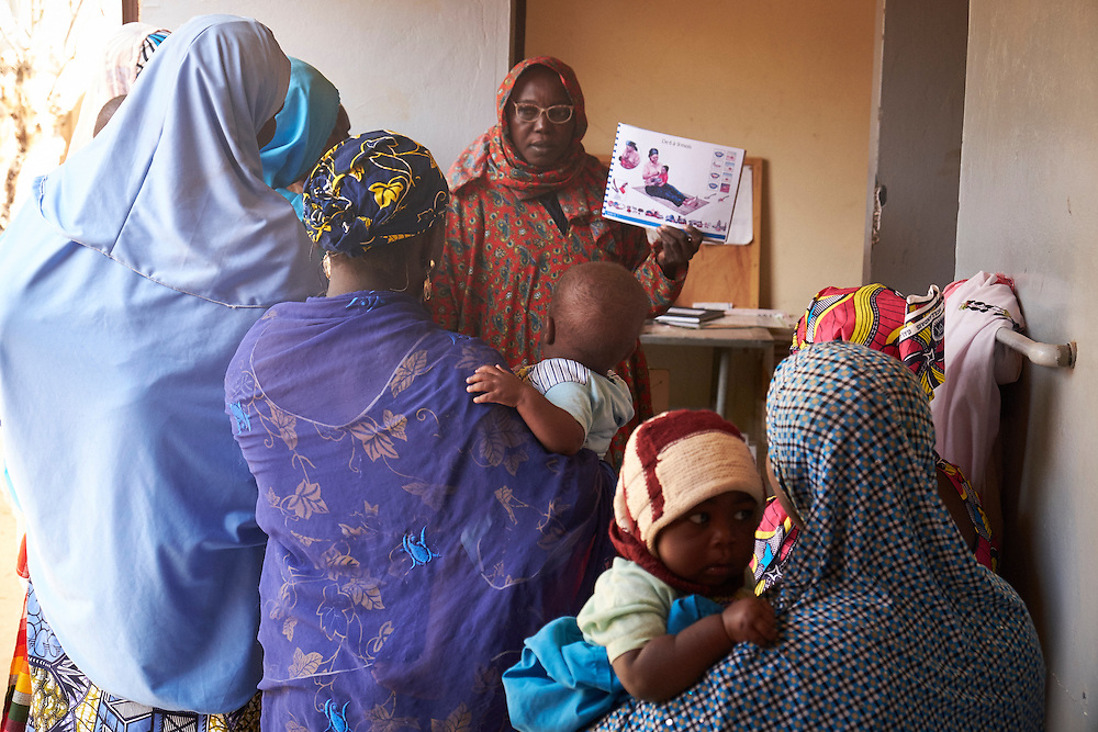 Mothers listen to a health worker undertake an awareness session on breastfeeding at the Saguia health centre, Niamey, Niger on February 16, 2016. The Saguia Health Centre serves a population of 9353 people thanks to a team of 20 people including 3 nurses and 4 midwives who receive pregnant women for prenatal consultations from Monday to Friday. During the first prenatal consultation the pregnant women receive a first dose of vaccinations and a booster on their second consultation. The third, fourth and fifth doses are administered later. This vaccination reinforces the immunity of the mothers and their children. The vaccination for against tetanus is free for pregnant women children under 5 years of age. To reach the population whom do not frequent health centres the district health department organise consultations in villages once per month that are more than 15km from the health centre.