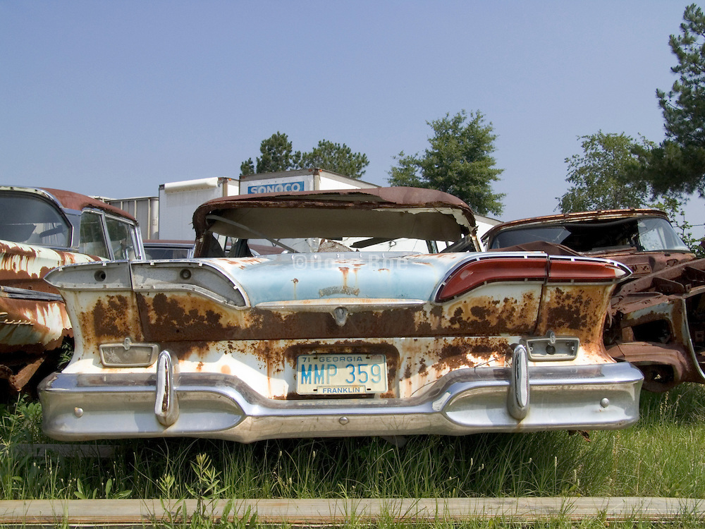 tail lights of classic cars sitting in a junkyard