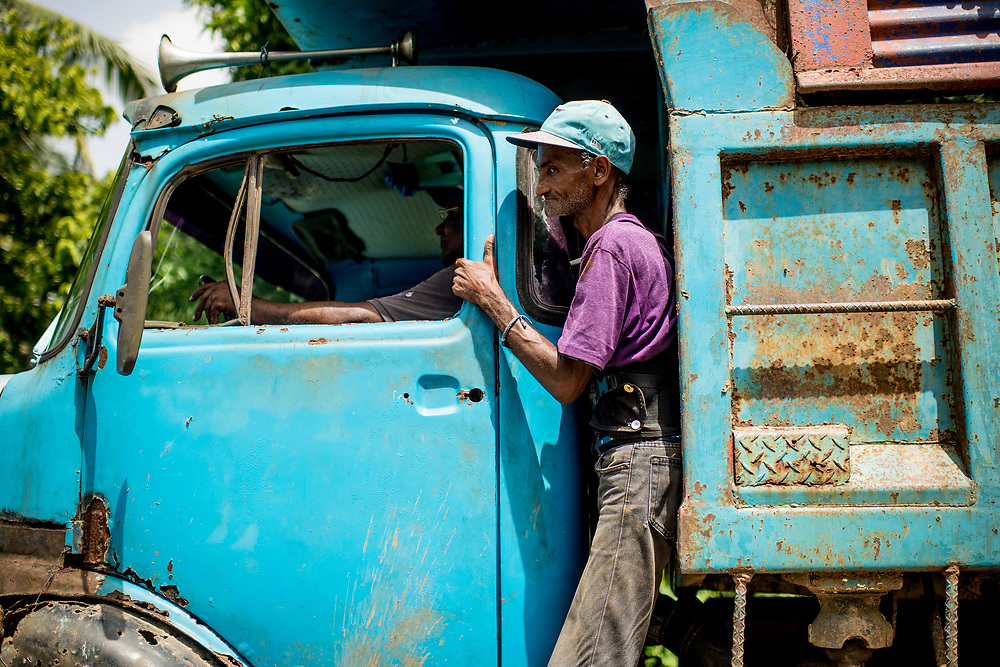 July 19, 2017, Boston, MA:<br /> A trash collector stands on a trash truck in El Mamon during the 2017 Lindos Sue&ntilde;os trip in the Dominican Republic Wednesday, July 19, 2017. <br /> (Photo by Billie Weiss/Boston Red Sox)