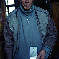 "CIZHONG, DECEMBER 17, 2000: Bernard, 75, holds a picture of Maurice Tournay,one of the French missionaries who built the Catholic church in Cizhong at then end of the 19th century, Yunnan province , December 17, 2000. Bernard went to jail for 22 years after the foreign missionaries left Cizhong in 1952 for having assisted them . he passed away in 2003..The church in Cizhong is believed to be the real life model for James Hilton's famous novel "" lost Horizon""- a description of Shangri-La-..Maurice Tournay is one of the catholic martyrs who were canonized by pope John Paul II on October 1, 2000.. ."