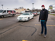 """11 APRIL 2020 - DES MOINES, IOWA: JASON CLARK , from Midwest Foods, directs traffic during a food distribution in Des Moines. Most non-essential businesses in Iowa are closed until 30 April. Because of business closings causes by the Novel Coronavirus (SARS-CoV-2) pandemic, well over 100,000 Iowans filed first time claims for unemployment in the last three weeks, more than applied during the peak of the Great Recession of 2008. Local food banks have seen an unprecedented spike in people seeking nutritional assistance. Midwest Foods, a Des Moines based company and owner of Ginos Fine Italian Foods, gave away 1,000 complete dinners with sauce, noodles, salad, and dressing Saturday morning. People started lining up 3 hours before the food distribution began. The food distribution was done following """"social distancing"""" guidelines and all of the workers wore masks and gloves.       PHOTO BY JACK KURTZ"""
