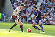 Sunderland Defender Billy Jones tries to tackle Tottenham Hotspur midfielder Nacer Chadli during the Barclays Premier League match between Sunderland and Tottenham Hotspur at the Stadium Of Light, Sunderland, England on 13 September 2015. Photo by Simon Davies.