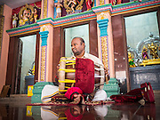 05 JUNE 2015 - KUALA LUMPUR, MALAYSIA:  A musician performs during midday prayers at Sri Mahamariamman Temple, the oldest functioning and most important Hindu temple in Malaysia. The principal deity in the temple is Mariamman,  a deity that is popularly worshipped by overseas Indians, especially Tamils, because she is looked upon as their protector during the sojourn to foreign lands. Mariamman is a manifestation of the goddess Parvati, an incarnation embodying Mother Earth with all her terrifying force. She is associated with disease and fever and protects her devotees from unholy or demonic events.    PHOTO BY JACK KURTZ