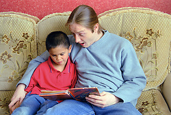 Father reading story book with young son,
