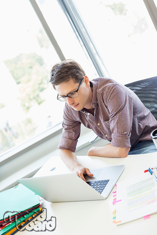 Creative businessman using laptop at desk in office