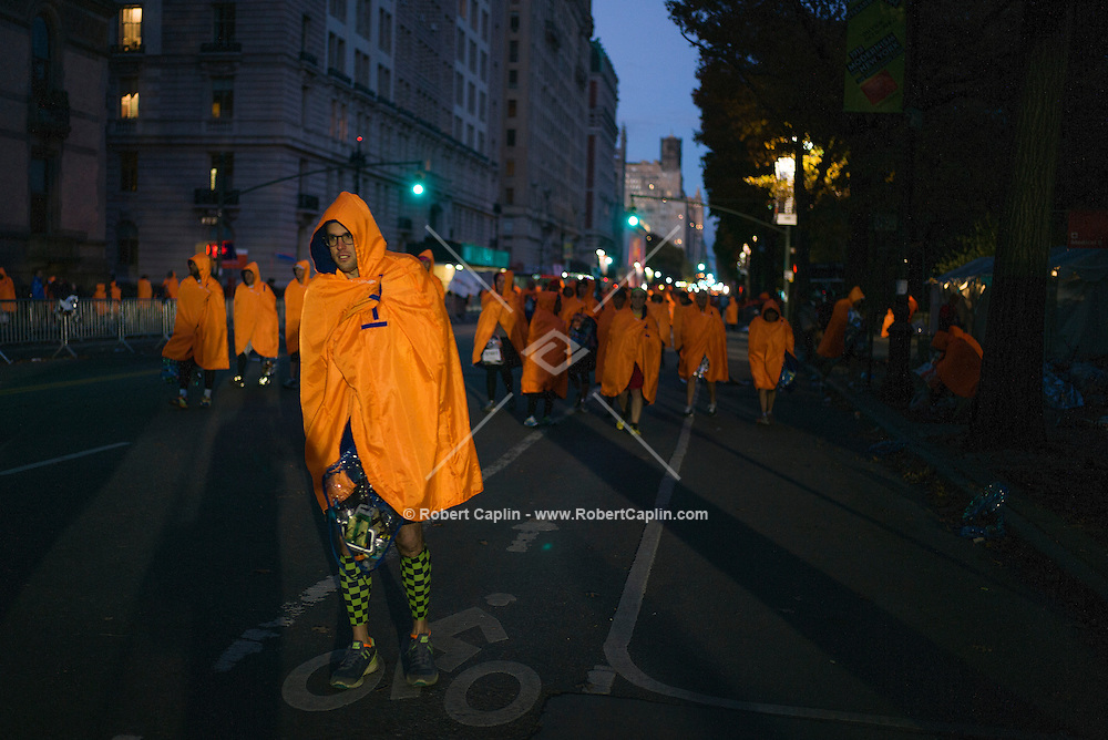 NEW YORK, NY &ndash; NOVEMBER 3, 2013: Marathon runners in orange ponchos after finishing the 2013 New York City Marathon.  <br /> <br /> Photo by Robert Caplin
