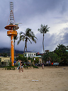 26 DECEMBER 2014 - PATONG, PHUKET, THAILAND: Tourists walk past a tsunami watch tower on Patong Beach in Patong, Phuket. Hundreds of people died in Patong and nearly 5400 people died on Thailand's Andaman during the 2004 Indian Ocean Tsunami that was spawned by an undersea earthquake off the Indonesian coast on Dec 26, 2004. In Thailand, many of the dead were tourists from Europe. More than 250,000 people were killed throughout the region, from Thailand to Kenya. There are memorial services across the Thai Andaman coast this weekend.    PHOTO BY JACK KURTZ