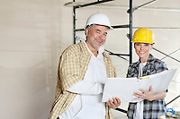 Portrait of happy team of architect with paper documents at construction site
