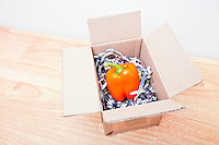 Orange bell pepper wrapped up in a box