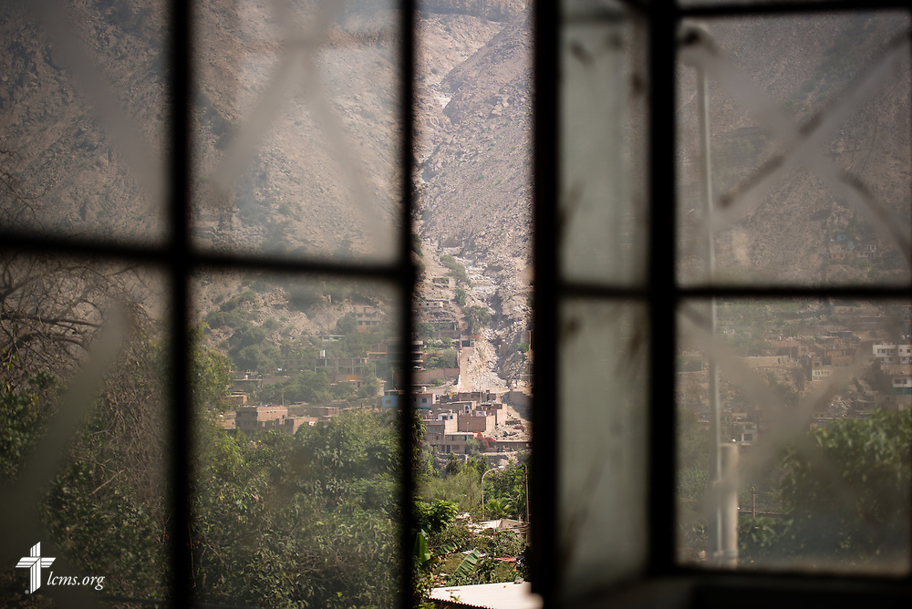 Landslides that devastated homes and businesses are seen from a window of the Noe (Spanish for Noah) school, one of many places also affected by the avalanches of mud and rock near Lima, Peru, on Tuesday, April 7, 2015. LCMS Communications/Erik M. Lunsford