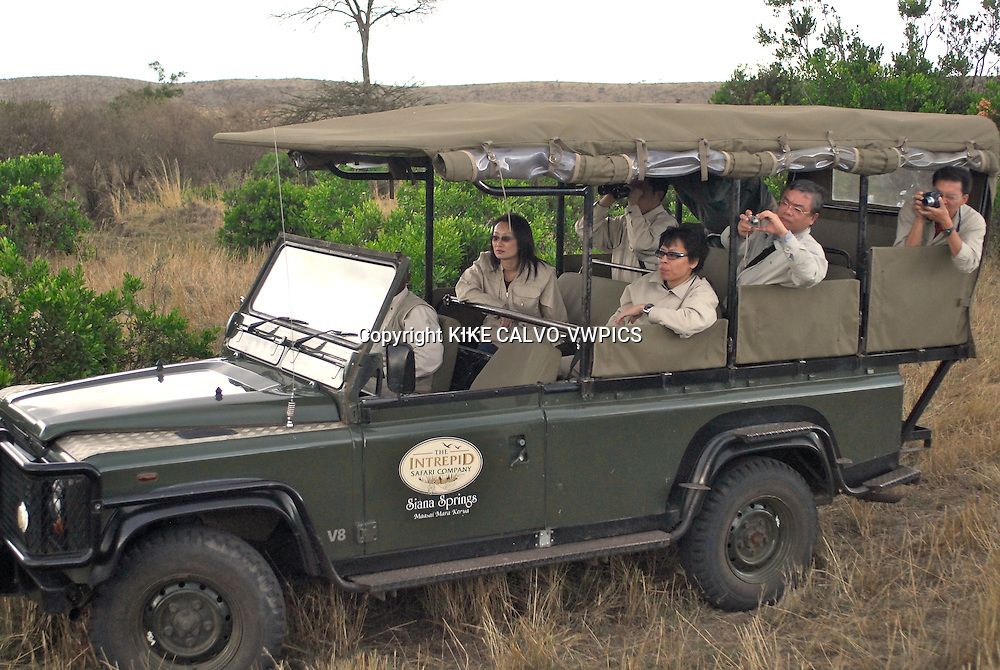 Tourist exploring Masai Mara National Park in Kenya on an open jeep