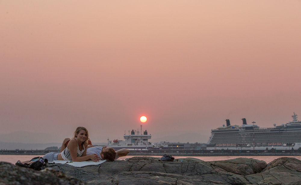 Denise Thompson and Zachary Davies enjoy the sunset at Holland Point Park below the Dallas Road Waterfront Trail in Victoria, British Columbia Canada on August 3, 2017. <br /> <br /> Smoke from wildfires in British Columbia&rsquo;s interior has drifted over Victoria and the lower mainland pushing air quality to a high risk level.