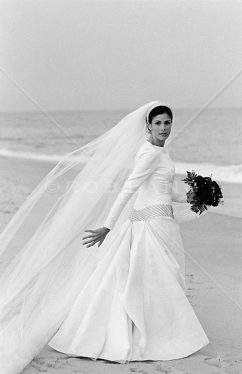 Bride in white gown walking on the beach in Westhampton, NY