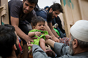 A toddler is lifted onto an Iraqi military vehicle to be transported with other civilians to a camp for internally displaced people near Mosul on May 19, 2017.
