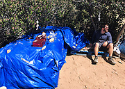 Ben Blain takes a break in the shade at the Third Gate Water Cache near mile 91 of the Pacific Crest Trail in Southern California on April 12, 2018. Beneath the blue tarps are gallons of potable water that have been placed here to support hikers on a dry section of desert trail. Without the water cache, hikers face a potential 24-mile section of trail without any water sources. First aid supplies left here also help soothe blistered feet and sunburnt skin, all common for hikers in the first 100 miles of the Pacific Crest Trail journey.
