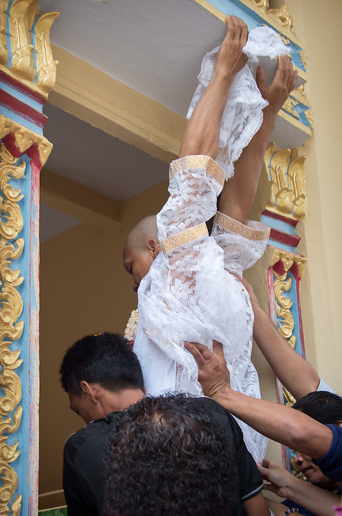Ting is lifted to touch the top of the entrance to the ordination hall for luck.