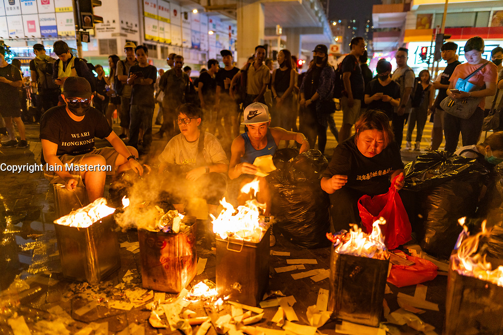 Hong Kong, China. 12th October 2019. Peaceful Pro-democracy march from tourist district of Tsim Sha Tsui along busy Nathan Road to Sham Shui Po Park in Kowloon. Some minor acts of vandalism to property were recorded but most marchers acted peacefully. Evening saw vigil at shrine at Prince Edward MTR  for protestor who died in police custody. People burning paper money for the spirits at shrine in traditional Chinese custom. Iain Masterton/Alamy Live News.