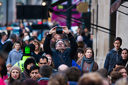 "London, December 20th 2014. Tens of thousands of shoppers descend on central London to scoop up pre-Christmas bargains as retailers offer discount incentives on ""Panic Saturday"". PICTURED: A shopper takes an overhead picture of the huge crowds on Regents Street with his smartphone."