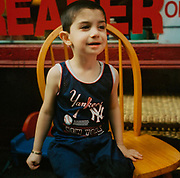 Little kid wearing a New York Yankees vest sitting on a chair USA