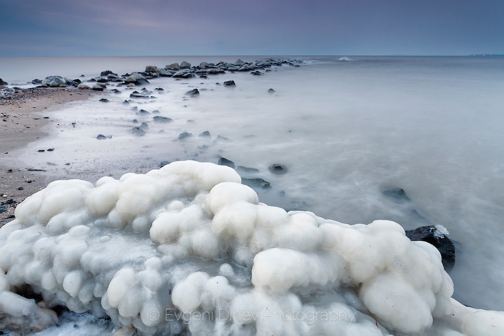 Frozen rocks by the sea at twilight