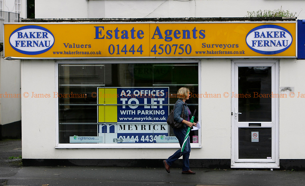 JAMES BOARDMAN / 07967642437<br /> A woman walks past an empty Estate Agents office up for rent in Haywards Heath West Sussex.