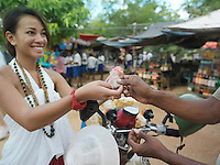 Young woman paying at street market smiling