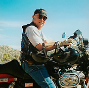 Old man sitting on his motorbike wearing a leather waistcoat and hat USA