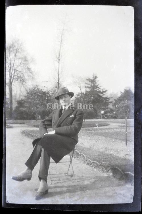 male person sitting in public park Paris 1900s