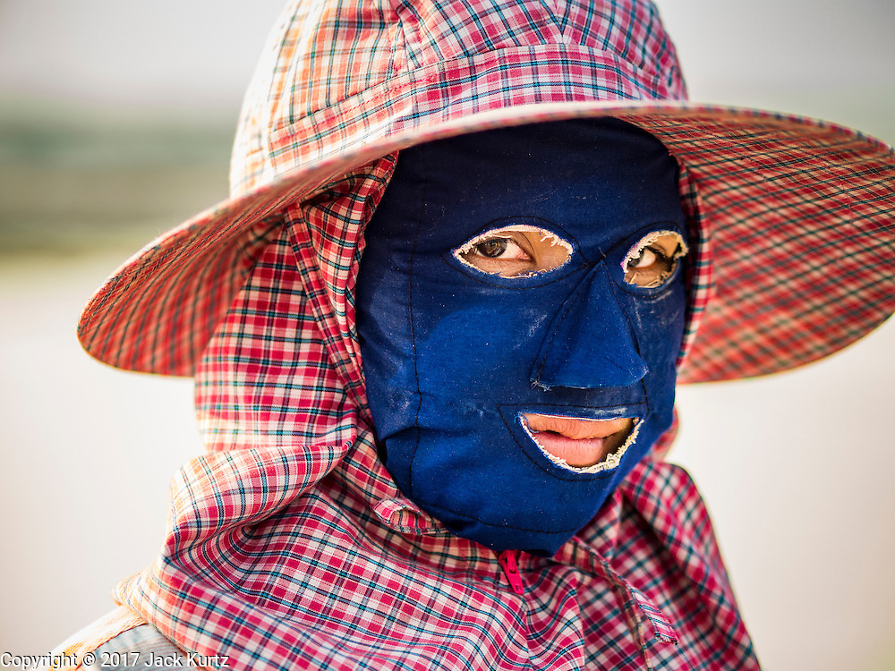 22 FEBRUARY 2017 - BAN LAEM, PETCHABURI, THAILAND: A salt field worker wearing a floppy hat and face mask for protection from the sun during the salt harvest in Petchaburi province of Thailand, about two hours south of Bangkok on the Gulf of Siam. Salt is collected in coastal flats that are flooded with sea water. The water evaporates and leaves the salt in large pans. Coastal provinces south of Bangkok used to be dotted with salt farms, but industrial development has pushed the salt farms down to remote parts of Petchaburi province. The harvest normally starts in early February and lasts until early May, but this year's harvest was delayed by a couple of weeks because of unseasonable rain in January that flooded many of the salt collection ponds.    PHOTO BY JACK KURTZ