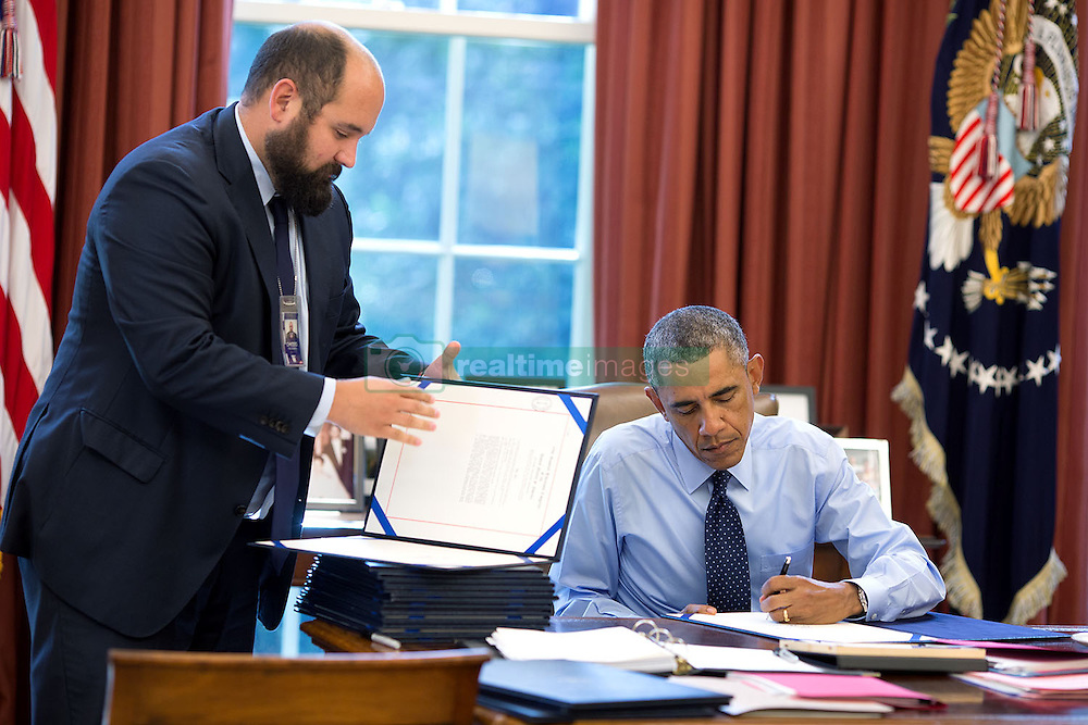 President Barack Obama, assisted by Deputy Staff Secretary Ted Chiodo, signs bills in the Oval Office, Sept. 26, 2014. (Official White House Photo by Pete Souza)<br /> <br /> This official White House photograph is being made available only for publication by news organizations and/or for personal use printing by the subject(s) of the photograph. The photograph may not be manipulated in any way and may not be used in commercial or political materials, advertisements, emails, products, promotions that in any way suggests approval or endorsement of the President, the First Family, or the White House.