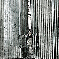 Construction worker peers from behind fence, Saigon, Vietnam