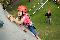 Young girl ascending the climbing wall at a Parklife summer activities event supervised by the Adventure activities event,