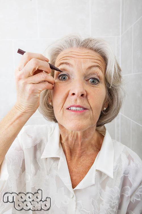 Portrait of senior woman applying eyeliner in bathroom