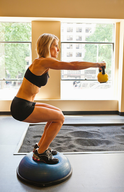Physically fit woman holding a bent knee sit position while extending a kettlebell in front of her.