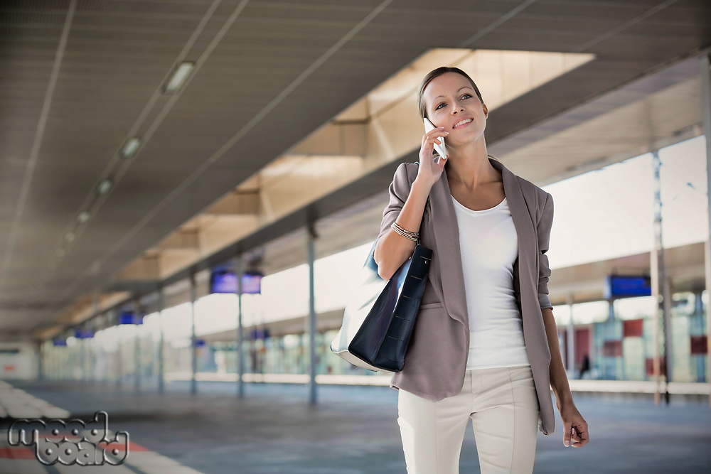 Portrait of young attractive businesswoman talking smartphone