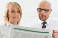 Mid adult business couple reading newspaper in kitchen