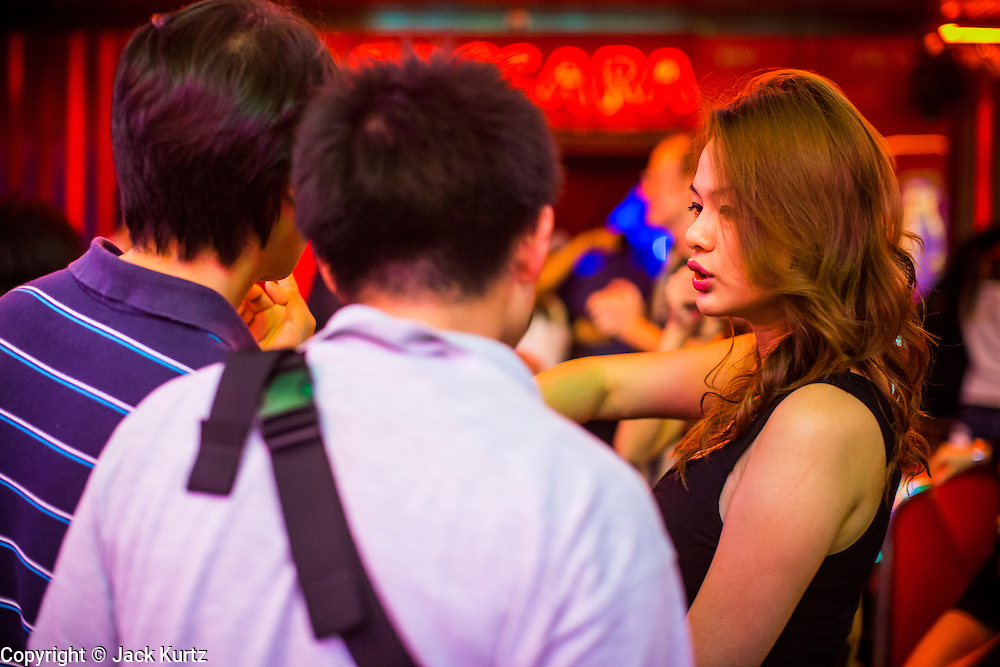 "12 JANUARY 2013 - BANGKOK, THAILAND:  A worker tries to draw tourists into Baccara, a go-go bar in the Soi Cowboy red light district. Prostitution in Thailand is illegal, although in practice it is tolerated and partly regulated. Prostitution is practiced openly throughout the country. The number of prostitutes is difficult to determine, estimates vary widely. Since the Vietnam War, Thailand has gained international notoriety among travelers from many countries as a sex tourism destination. One estimate published in 2003 placed the trade at US$ 4.3 billion per year or about three percent of the Thai economy. It has been suggested that at least 10% of tourist dollars may be spent on the sex trade. According to a 2001 report by the World Health Organisation: ""There are between 150,000 and 200,000 sex workers (in Thailand).""    PHOTO BY JACK KURTZ"