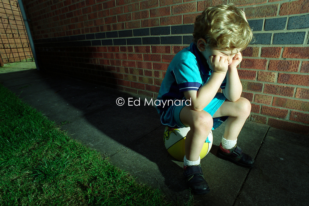Four year old boy sat on a basketball, looking fed up and bored, England, UK.