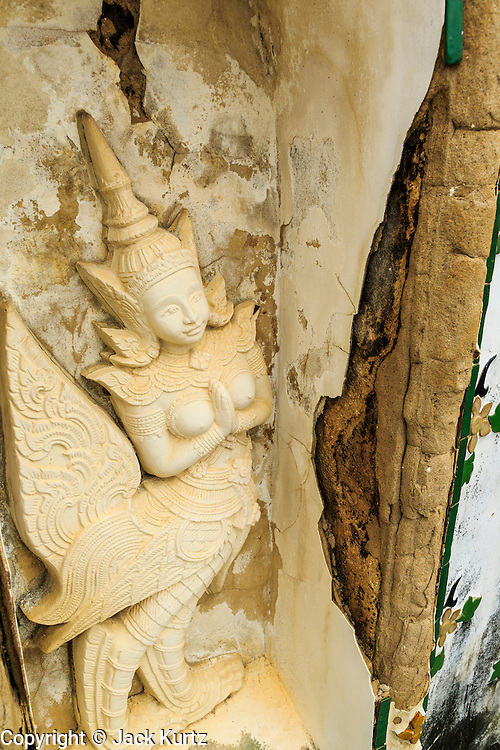 "23 SEPTEMBER 2013 - BANGKOK, THAILAND:   An angel at Wat Arun. The angel figures are scheduled to be renovated by Thai artisans during the renovation of the temple. The full name of the temple is Wat Arunratchawararam Ratchaworamahavihara. The outstanding feature of Wat Arun is its central prang (Khmer-style tower). The world-famous stupa, known locally as Phra Prang Wat Arun, will be closed for three years to undergo repairs and renovation along with other structures in the temple compound. This will be the biggest repair and renovation work on the stupa in the last 14 years. In the past, even while large-scale work was being done, the stupa used to remain open to tourists. It may be named ""Temple of the Dawn"" because the first light of morning reflects off the surface of the temple with a pearly iridescence. The height is reported by different sources as between 66,80 meters and 86 meters. The corners are marked by 4 smaller satellite prangs. The temple was built in the days of Thailand's ancient capital of Ayutthaya and originally known as Wat Makok (The Olive Temple). King Rama IV gave the temple the present name Wat Arunratchawararam. Wat Arun officially ordained its first westerner, an American, in 2005. The central prang symbolizes Mount Meru of the Indian cosmology. The temple's distinctive silhouette is the logo of the Tourism Authority of Thailand.         PHOTO BY JACK KURTZ"