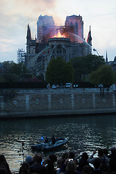 People looking at the flame with police boat on the seine. Bystanders look on as flames and smoke are seen billowing from the roof at Notre-Dame Cathedral with river in Paris on April 15, 2019. A fire broke out at the landmark Notre-Dame Cathedral in central Paris, potentially involving renovation works being carried out at the site, the fire service said.Images posted on social media showed flames and huge clouds of smoke billowing above the roof of the gothic cathedral, the most visited historic monument in Europe. Photo by Raphael Lafargue/ABACAPRESS.COM
