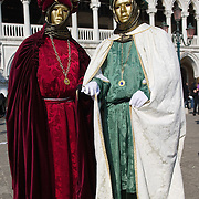 VENICE, ITALY - FEBRUARY 26:  Two men wearing Carnival costumes and masks pose in St Mark Square with the background of Palazzo Ducale on February 26, 2011 in Venice, Italy.  The Venice Carnival, one of the largest and most important in Italy, attracts thousands of people from around the world each year. The  theme for this year's carnival is 'Ottocento', a nineteenth century evocation, and will run from February 19 till March 8.