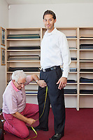 Senior tailor getting customers measurement