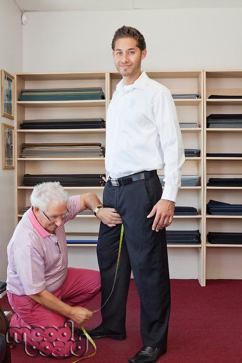 Senior tailor getting customers measurement