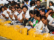 """02 JANUARY 2016 - KHLONG LUANG, PATHUM THANI, THAILAND: People pray at Wat Phra Dhammakaya on the first day of the 5th annual Dhammachai Dhutanaga (a dhutanga is a """"wandering"""" and translated as pilgrimage). More than 1,300 monks are participating pilgrimage through central Thailand. The purpose of the pilgrimage is to pay homage to the Buddha, preserve Buddhist culture, welcome the new year, and """"develop virtuous Buddhist youth leaders."""" Wat Phra Dhammakaya is the largest Buddhist temple in Thailand and the center of the Dhammakaya movement, a Buddhist sect founded in the 1970s. The monks are using busses on some parts of the pilgrimage this year after complaints about traffic jams caused by the monks walking along main highways.          PHOTO BY JACK KURTZ"""