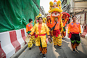 "09 FEBRUARY 2013 - BANGKOK, THAILAND:  Chinese Lion Dancers walk down a sidestreet in Chinatown in Bangkok. Bangkok has a large Chinese emigrant population, most of whom settled in Thailand in the 18th and 19th centuries. Chinese, or Lunar, New Year is celebrated with fireworks and parades in Chinese communities throughout Thailand. The coming year will be the ""Year of the Snake"" in the Chinese zodiac.   PHOTO BY JACK KURTZ"