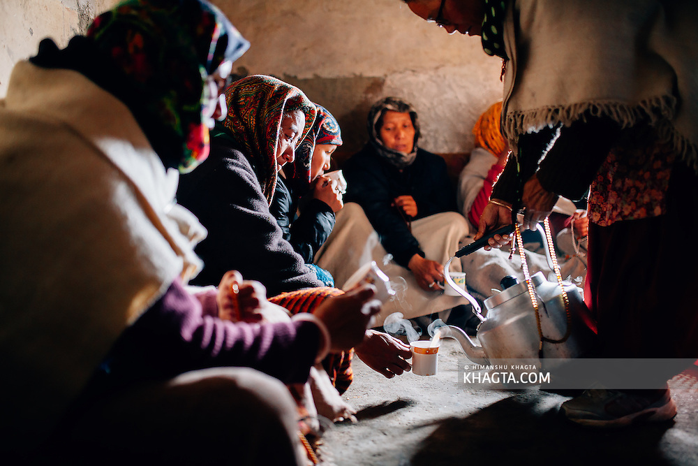 Women of Spiti, chanting together in the village prayer hall as tea is being served to them. In the winter months, Spiti people spend a lot of time  in religious activities.