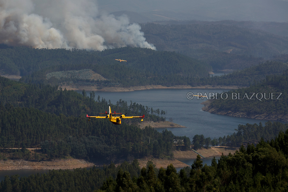 LEIRIA, PORTUGAL - JUNE 20:  Firefighter planes work on a fire after a wildfire took dozens of lives on June 20, 2017 near Pedrogao Grande, in Leiria district, Portugal. On Saturday night, a forest fire became uncontrollable in the Leiria district, killing at least 64 people and leaving many injured. Some of the victims died inside their cars as they tried to flee the area.  (Photo by Pablo Blazquez Dominguez/Getty Images)
