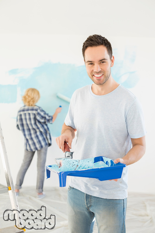 Portrait of man holding paint roller and tray with woman painting wall in background