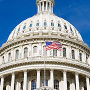 The US Capitol Building on Capitol Hill in Washington DC. Home to United States Congress, it's distinctive dome at the center fo the building, between the House of Representatives wing and the Senate wing, towers over the city of Washington DC and can be seen from miles around.