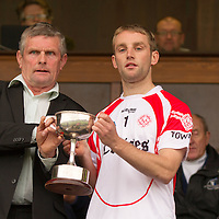 Éire Óg captain Kevin Brennan being presented withthe Senior B Final Cup by Cllr. Joe Cooney